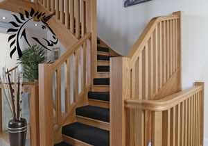 Bespoke Staircases in oak the manhattan staircase with half black carpet detail